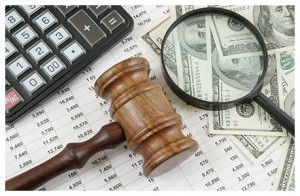 judge's gavel, calculator, hundred dollar bills and magnifying glass