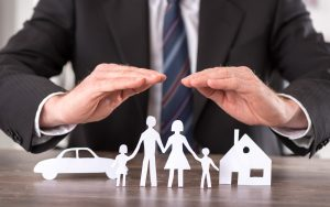 an attorney with cupped hands over paper cut outs of family, home and car