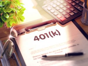 401 K paperwork on the desk with a calculator and pen